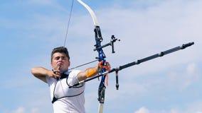 El arquero de sexo masculino está tirando después de apuntar Tiroteo con un arco y las flechas almacen de video