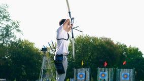 El arquero de sexo masculino está utilizando el arco para apuntar Tiroteo del tiro al arco almacen de metraje de vídeo