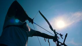 El arquero está tirando de la cuerda de arco en la luz del sol Tiroteo con un arco y las flechas metrajes