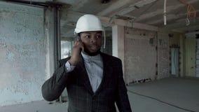 El arquitecto africano joven pasa a través de las premisas del edificio reparado, hablando en el smartphone almacen de metraje de vídeo