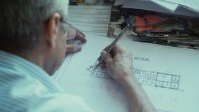 El arquitecto aplica los compases que dibujan y dibuja una línea en lápiz almacen de metraje de vídeo