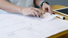 El arquitecto de la mujer está trabajando con los dibujos que se sientan por la tabla, primer de las manos metrajes
