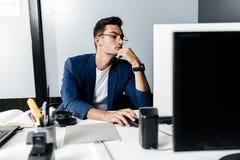 El arquitecto del hombre joven en los vidrios vestidos en un traje de negocios se sienta en un escritorio delante de un ordenador imagen de archivo