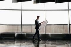 El arquitecto en ropa elegante sostiene la hoja con el dibujo en su mano y negociaciones al lado del teléfono en el fondo de un v imágenes de archivo libres de regalías