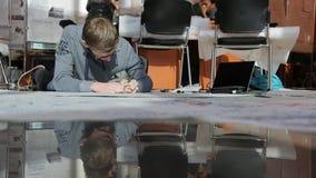 El arquitecto en sudadera con capucha gris miente en piso y dibuja el proyecto del edificio almacen de metraje de vídeo