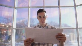 El arquitecto joven mira esquemas mientras que se coloca en oficina almacen de metraje de vídeo
