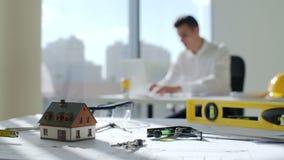 El arquitecto moreno joven se sienta por la tabla cerca de una ventana grande en la empresa de la construcción blanca de la ofici