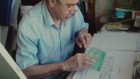 El arquitecto pone un prolongador para dibujar la línea y el dibujo en lápiz almacen de video