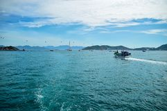 El arrastrero de la pesca vuelve al puerto, contra el contexto del zaoiva, de naves, del teleférico, de montañas y de nubes foto de archivo