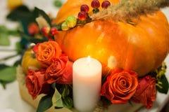 El arreglo brillante del otoño de flores y de bayas en la calabaza imagen de archivo libre de regalías