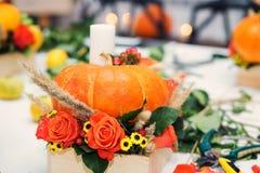 El arreglo brillante del otoño de flores y de bayas en la calabaza fotografía de archivo libre de regalías