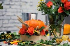 El arreglo brillante del otoño de flores y de bayas en la calabaza imagenes de archivo