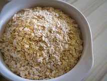 El arroz de la avena en el cuenco blanco en la imagen de madera del tono del gusano de la tabla superior fotos de archivo