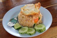 El arroz frito y los huevos fritos en el top con adornan el pepino y la cal (la vista posterior) de la rebanada Imagenes de archivo
