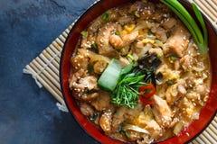 El arroz japonés de Oyakodon encendido remató con el pollo, el huevo, la cebolla, y la alga marina en cuenco de arroz de cerámica Fotos de archivo