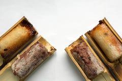 El arroz pegajoso asó en el cuatro-pedazo de bambú en un backgroun blanco imagenes de archivo
