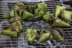 El arroz pegajoso envuelto en las hojas del plátano, asadas en la parrilla es una comida popular en Tailandia foto de archivo