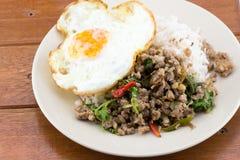 El arroz remató con albahaca sofrita del cerdo y el huevo frito fotografía de archivo