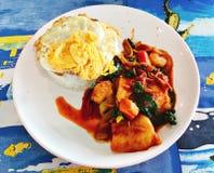 El arroz remató con el huevo frito, mariscos sofritos picantes con goma roja del curry fotografía de archivo libre de regalías