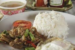 El arroz remató el cerdo del sofrito con albahaca y el huevo frito Foto de archivo