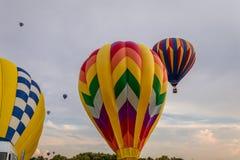 El arsenal colorido de globos del aire caliente flota a través del cielo en la oscuridad en el ` s de Warren County Farmer favora Fotos de archivo
