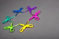 El arte brillantemente coloreado scissors la colocación en un fondo gris en la forma de una estrella Imagen de archivo