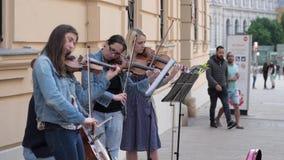 El arte de la calle, mujeres de los violinistas juega en los instrumentos musicales para los transeúntes en ciudad almacen de metraje de vídeo
