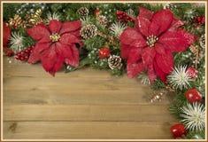 El arte de la Navidad adornó la poinsetia de la tarjeta encima de la madera Fotografía de archivo libre de regalías