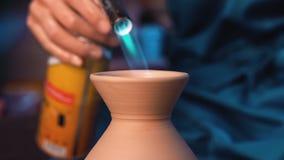 El artesano acaba la creación del jarro de la arcilla en su taller El hombre quema el producto usando el arma de la hornilla de l almacen de video
