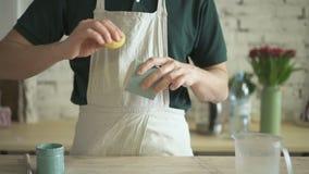 El artesano con la esponja borra suavemente exceso de pintura de la parte inferior de la taza de la arcilla almacen de metraje de vídeo