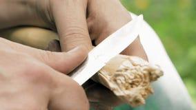 El artesano da la talla de la barra de madera con un cuchillo metrajes