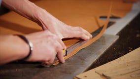 El artesano de cuero corta el borde del producto con un cuchillo de modo que sea uniforme almacen de video