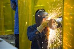 El artesano de la soldadura que muele el tubo de acero Imagen de archivo