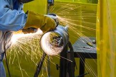 El artesano de la soldadura que muele el tubo de acero imágenes de archivo libres de regalías