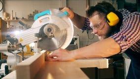 El artesano está cortando la madera con una sierra rotatoria en la cámara lenta metrajes