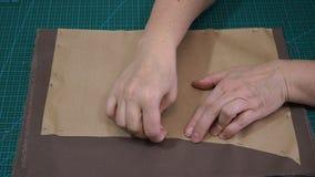 El artesano fija el modelo de papel a la tela metrajes