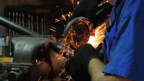 El artesano Working With una sierra circular, chispas vuela de fundición El trabajo duro de los hombres Hombre trabajado en el ac almacen de video