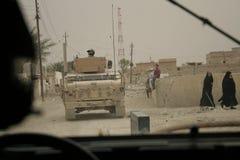 El artillero conecta con los niños iraquíes durante patrulla Imagen de archivo libre de regalías