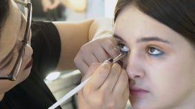 El artista asiático del rostro está haciendo compensa el modelo femenino joven en estudio, cierre para arriba almacen de metraje de vídeo