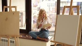 El artista atractivo se sienta en el alféizar con un cepillo y la paleta en sus manos almacen de video