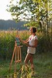 El artista bonito joven de la mujer dibuja las pinturas una imagen del lago en aire libre llano abierto del aire foto de archivo