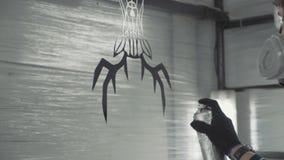 El artista colorea el detalle decorativo del metal en su taller metrajes