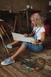 El artista con el pelo multicolor en pinturas pintura-manchadas de los vaqueros Imágenes de archivo libres de regalías