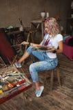 El artista con el pelo multicolor en pinturas pintura-manchadas de los vaqueros Fotografía de archivo libre de regalías