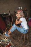 El artista con el pelo multicolor en pinturas pintura-manchadas de los vaqueros Imagenes de archivo