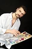 El artista creativo con la paleta y los cepillos mira hacia foto de archivo