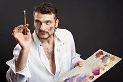 El artista creativo con la paleta y los cepillos mira hacia imagenes de archivo