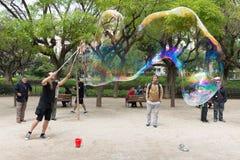 El artista de la calle hace burbujas de jabón grandes Foto de archivo libre de regalías
