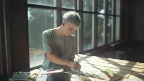 El artista de la calle trabaja en estudio con la ventana panorámica en un podio de madera almacen de video