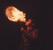 El artista de la demostración del fuego respira el fuego en la oscuridad fotos de archivo libres de regalías